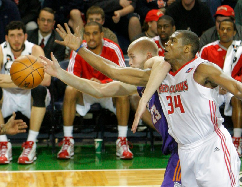 Justin Brownlee of the Maine Red Claws, 34, and Michael Tveidt of the Iowa Energy get tangled up while competing for a loose ball Friday night. The Red Claws held a 21-point lead midway through the third quarter, then lost.