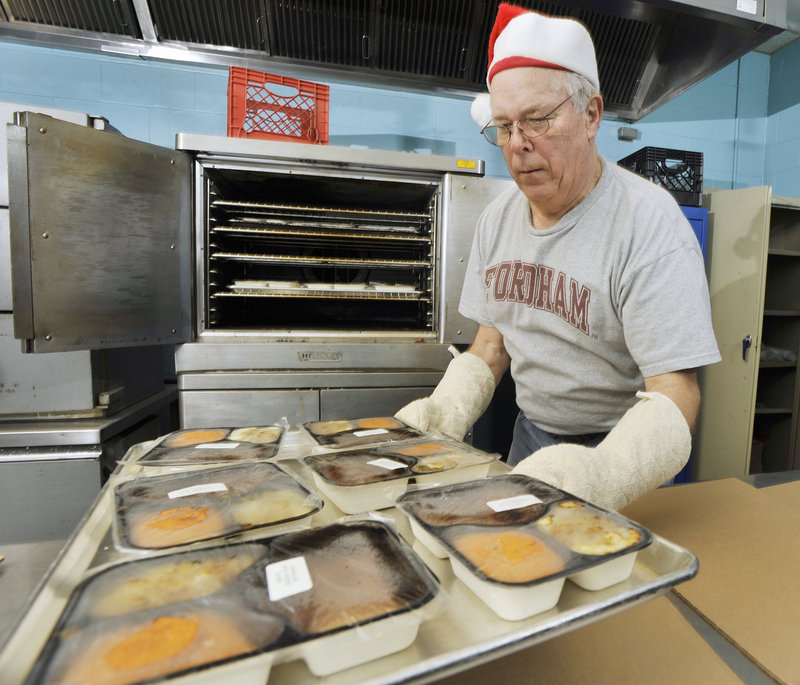 Tom O'Connor of Portland pulls trays of prepared meals from the oven where they were heated before being delivered Sunday.