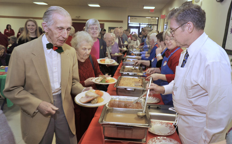 Bill Tolman, left, makes his way through the serving line at the annual holiday dinner hosted by Westbrook-Warren Congregational Church. About 300 people were fed this year.