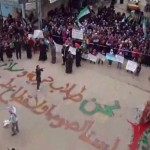 """An amateur video shot Friday shows protesters gathered in Homs, Syria. The writing on the ground, in Arabic, reads : """"We are those who seek freedom and peace. We are not thieves or outlaws."""""""