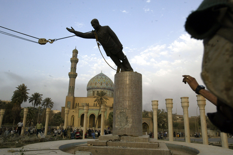 A U.S. Marine watches a statue of Saddam Hussein being toppled in downtown Baghdad in April 2003.