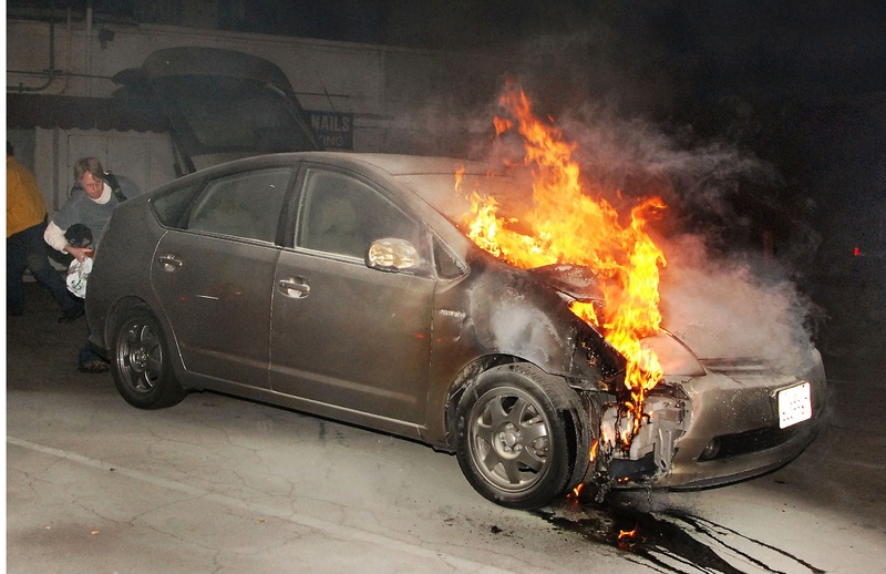 A car owner tries to retrieve possessions from his vehicle as it burns due to arson early Monday in a parking lot in Los Angeles. Eleven more suspected arson fires burned early Monday in the city.