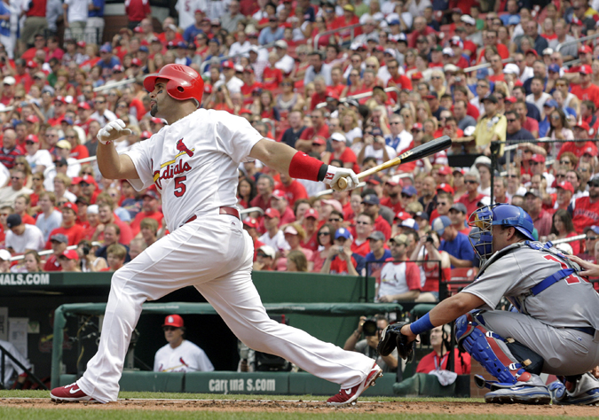 In this July 30, 2011, photo, then-St. Louis Cardinals first baseman Albert Pujols follows through on a solo home run in a game against the Chicago Cubs.