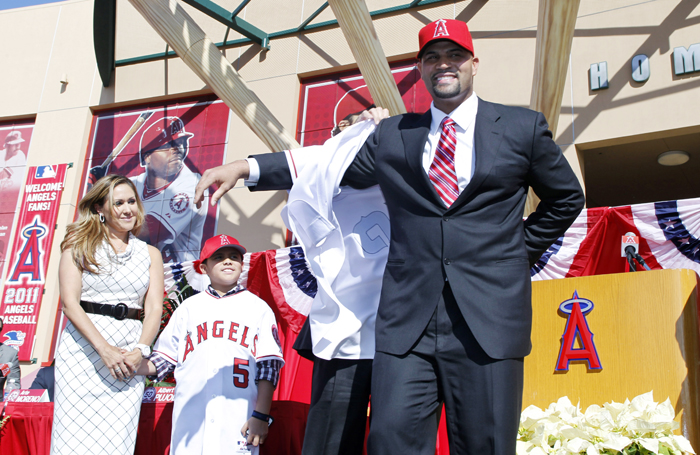 Los Angeles Angels' Albert Pujols puts on his new jersey as his wife Deidre Pujols, left, and his son Alberto Pujols Jr. look on during a baseball news conference in Anaheim on Dec. 12, 2011.