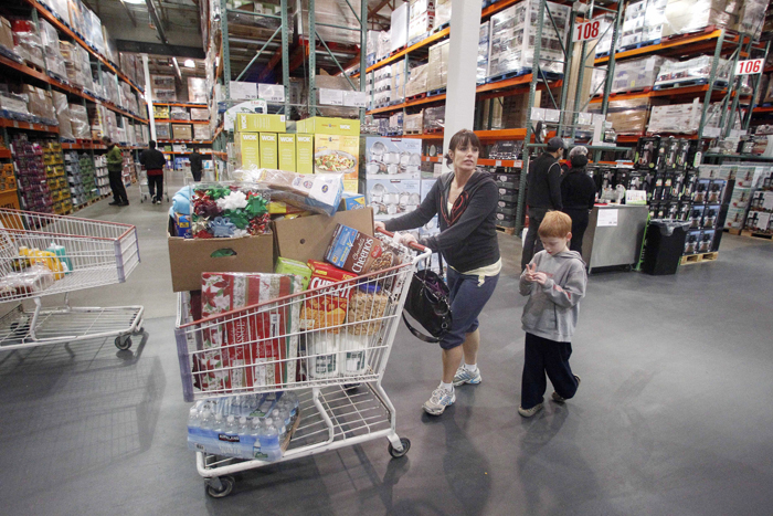 Jenni Weber and her son Jacob, 7, of Portland, Ore., shop at a Costco store recently. Costco's revenue at stores open at least a year rose 7 percent in December.