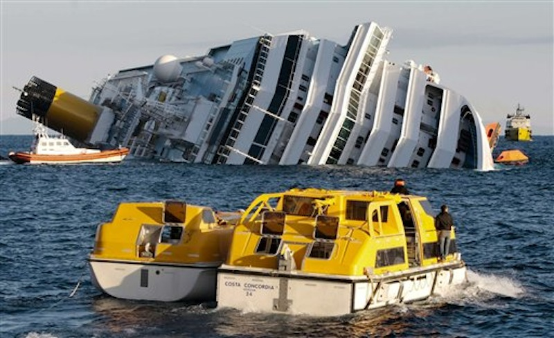 Investigators on Sunday approach the luxury cruise ship Costa Concordia which leans on its starboard side after running aground in Italy. (AP Photo/Gregorio Borgia)