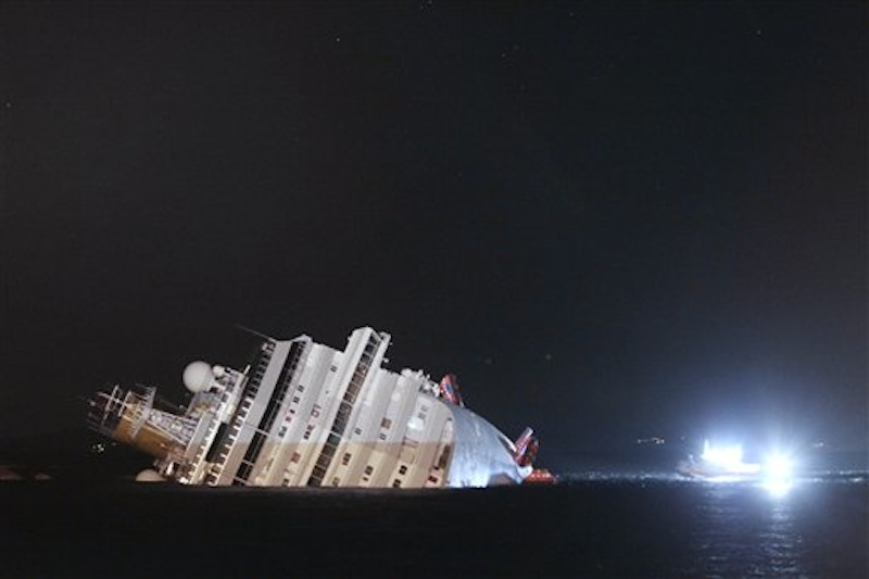 The luxury cruise ship Costa Concordia leans on its side after running aground the tiny Tuscan island of Giglio, Italy, Saturday, Jan. 14, 2012. The ship ran aground off the coast of Tuscany, sending water pouring in through a 160-foot (50-meter) gash in the hull and forcing the evacuation of some 4,200 people from the listing vessel early Saturday. (AP Photo/Gregorio Borgia)