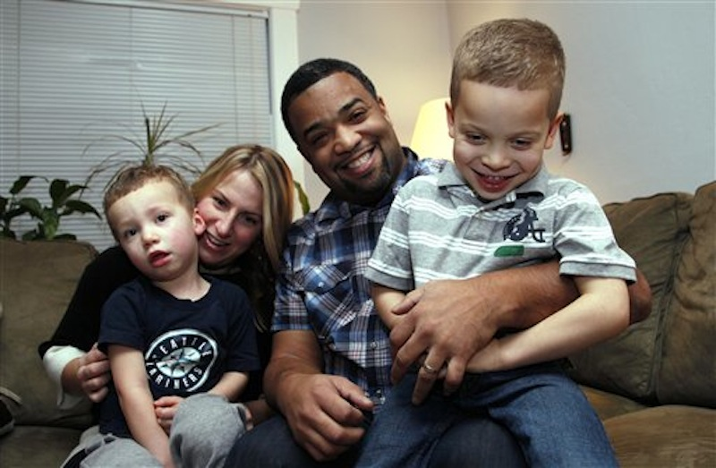 "In this Dec. 27 photo, Damon Brown sits with his wife, Bethany, as they hold their sons Theo, 3, left, and Julian, 5, at their home in Seattle. Damon Brown found a kidney on Facebook after telling his story on a special page the Seattle dad created under the name, ""Damon Kidney"". (AP Photo/Elaine Thompson)"