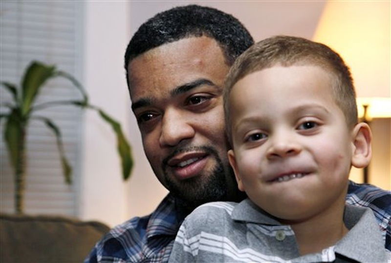 In this Dec. 27, 2011, Damon Brown sits with his son Julian, 5, at their home in Seattle. (AP Photo/Elaine Thompson)