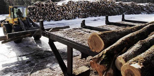 Logs are moved around the wood yard at Southern Maine Firewood in Gorham recently. The company sold 3,200 cords last year, up from 2,600 in 2010.