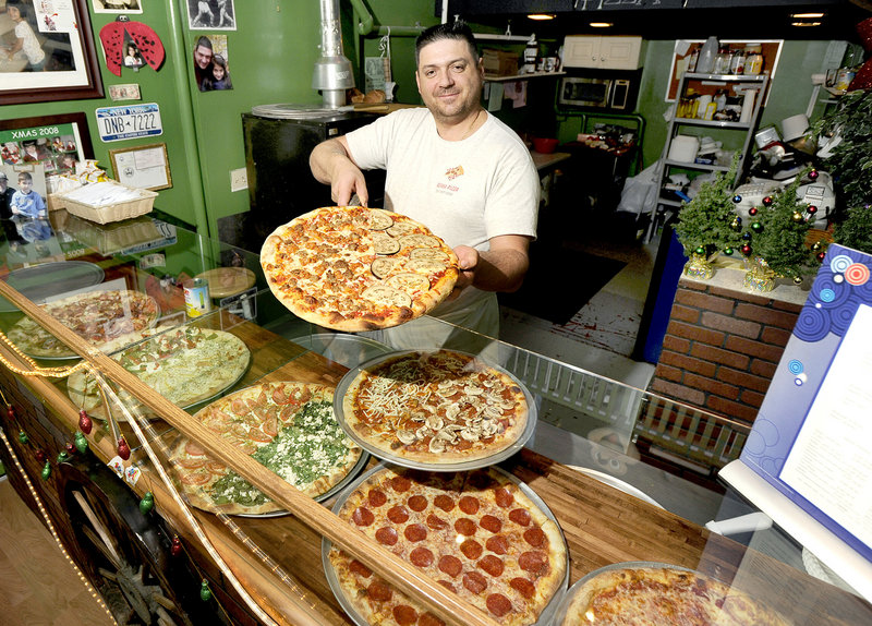 Owner Luca Pizzuti shows off a meat lover and eggplant rollatini pizza at Roma Pizza in Portland.
