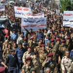 """Yemeni soldiers and officers march during a rally in the southern city of Taiz on Saturday, demanding reforms and the dismissal of a senior official over allegations of corruption. The banners read, """"Take from me the rifle and give me the civil state,"""" and """"With our standing against corruption, we will build an army to protect the country."""""""