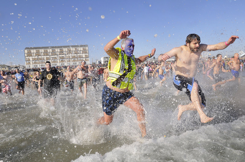 Peter MacVane, center, a founder of the fundraiser, leads the plunge in the 24th annual Lobster Dip in Old Orchard Beach on Sunday. The temperatures – 43 degrees for the air and 45 for the water – made it a bit easier than past New Year's Day dips.