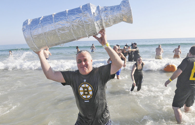 Don Hill of Team Brunswick hoists a fake Stanley Cup after his dip at Old Orchard Beach.