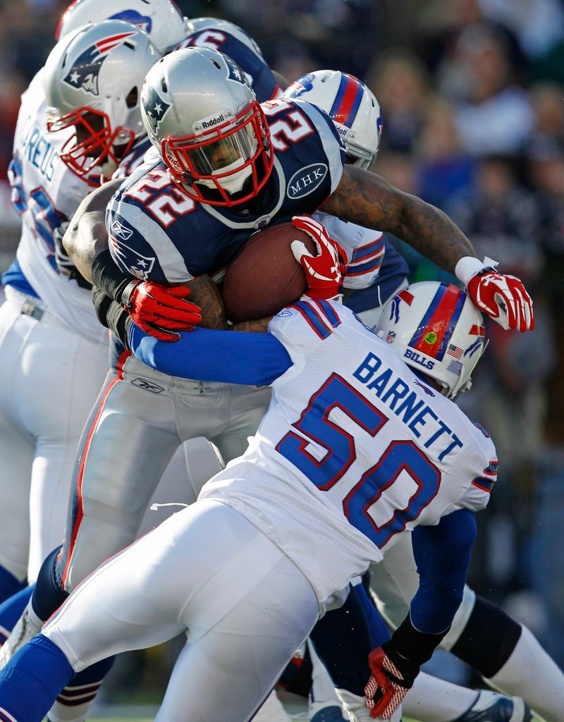 Stevan Ridley of the Pats, who led the team with 81 rushing yards on 15 carries, gets stopped by Buffalo's Nick Barnett in Sunday's game at Gillette Stadium.