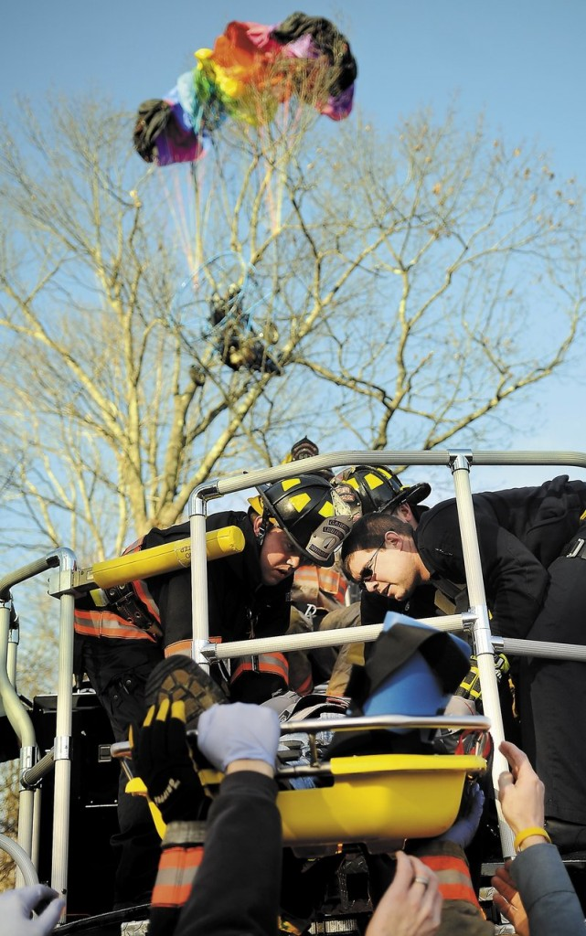 Firefighters and police lower John Beganny to the ground Sunday after rescuing him from a tree in Litchfield.