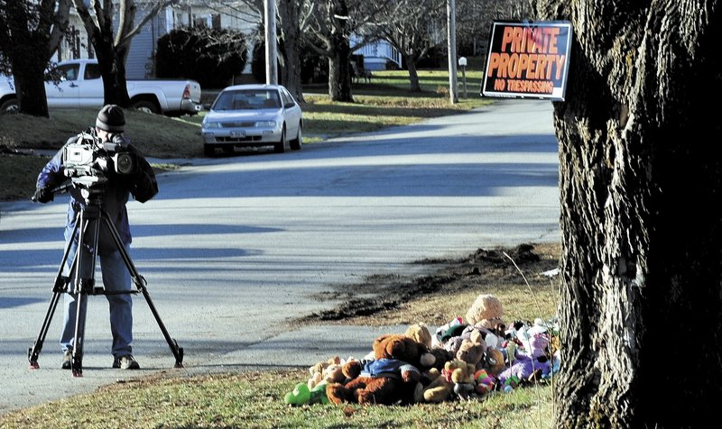 A television news photographer films a pile of stuffed animals Monday below a no-trespassing sign at the home at 29 Violette Ave. in Waterville where Ayla Reynolds was reported missing since Dec. 17. Her father, Justin DiPietro, is pleading for her safe return.