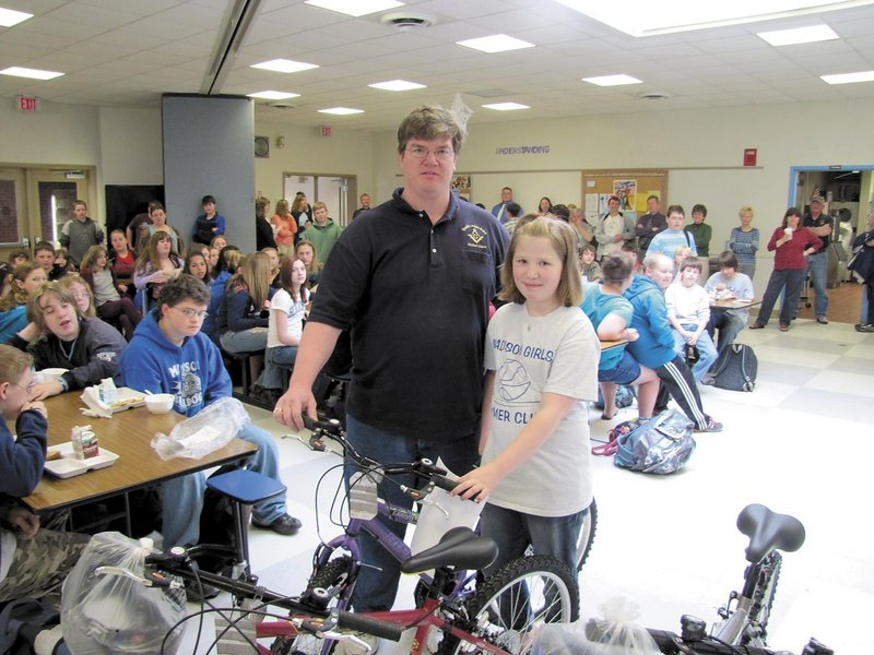 Madeline Theriault, 11, of Madison, stands with dad Mike Theriault and the bicycle she won last spring.