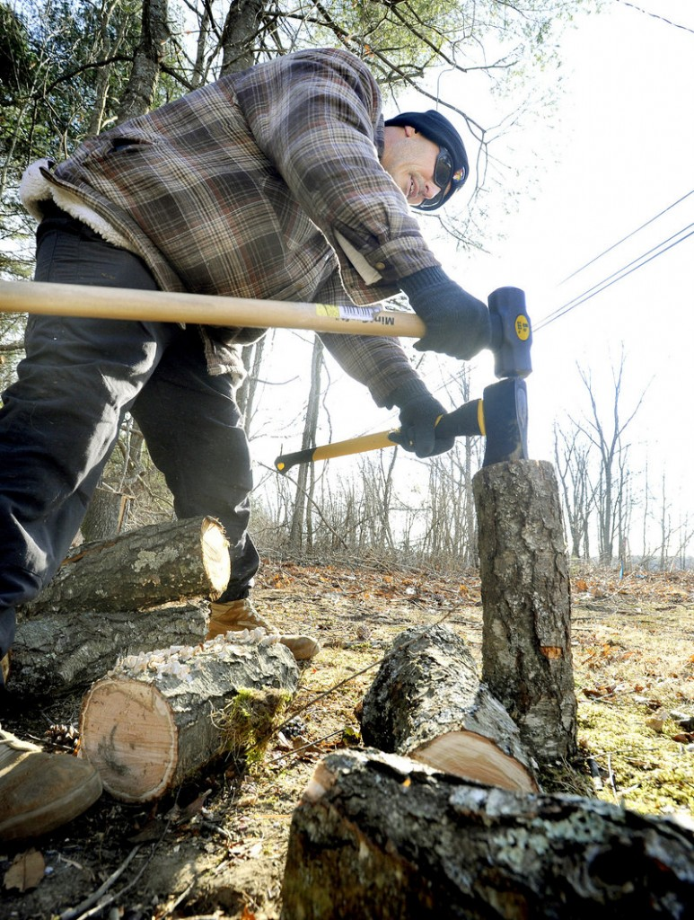 Saco resident Seamus Garrett splits logs to burn in his fireplace Wednesday during the winter's coldest months.