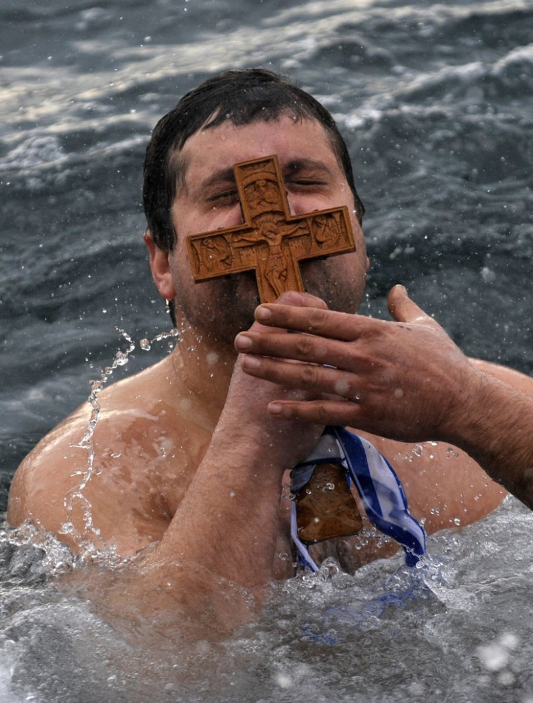 Panagiotis Mantziaris kisses the wooden cross after being the first to retrieve it Friday during an Epiphany ceremony to bless the water in Greece's northern port city of Thessaloniki.