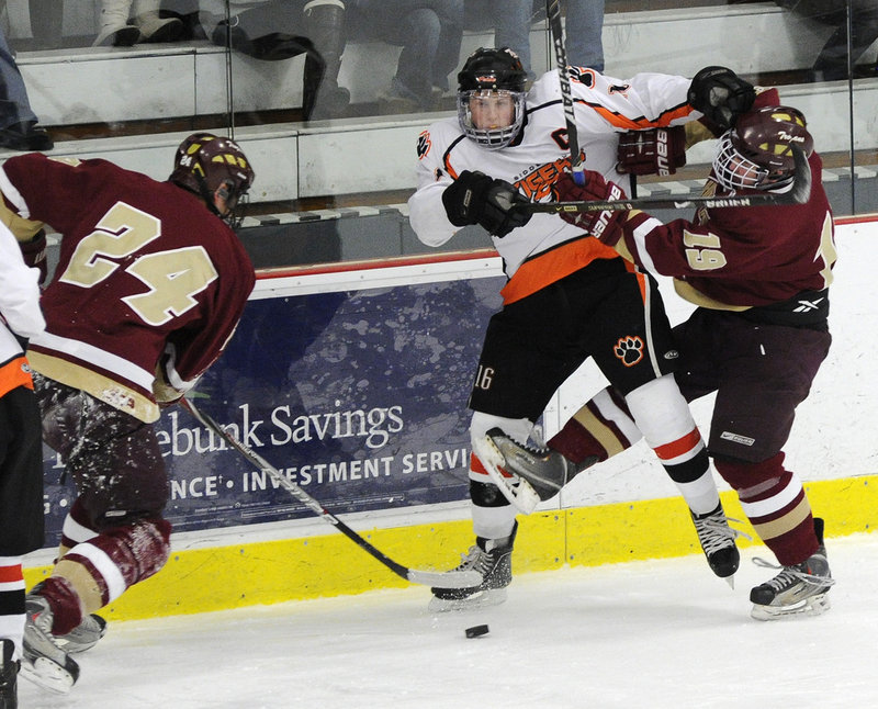 Tyler Danley, left, of Thornton Academy takes control of the puck as his teammate, Robbie Downing, ties up Taylor Reuillard of Biddeford during their game at the Biddeford Ice Arena.