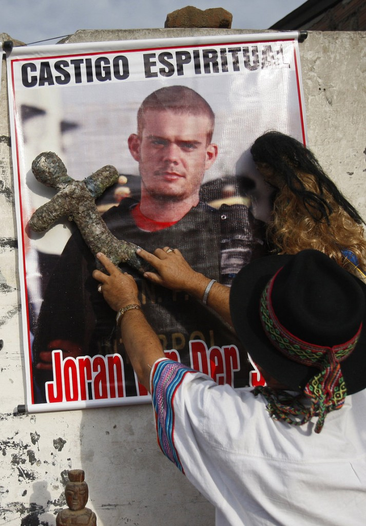A shaman performs a ritual for the spiritual punishment of Joran van der Sloot, whose picture is posted on the wall, before Van der Sloot's trial opened in Lima, Peru, on Friday.