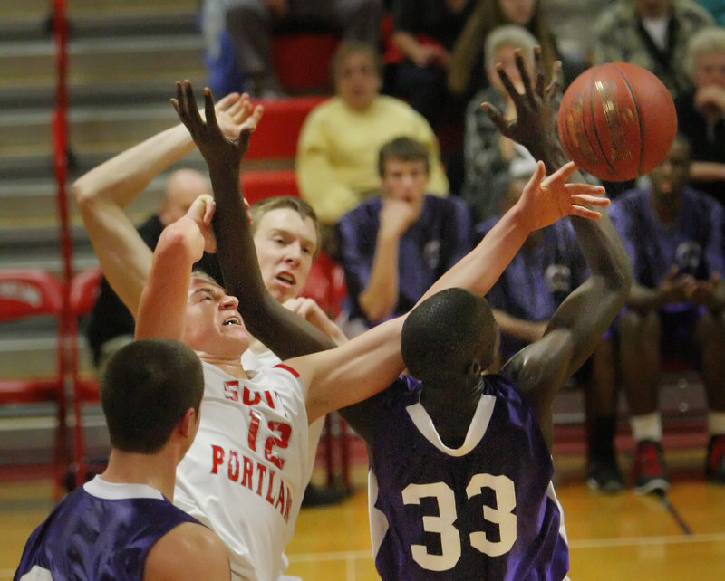 Ben Burkey of South Portland, left, and Labson Abwoch of Deering contend for a rebound during their physical game Friday night. Unbeaten Deering earned a 40-29 victory.