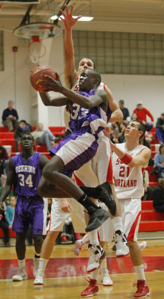 The path to the basket was never easy Friday night: Labson Abwoch of Deering looks for a way to slip past Jack Tolan of South Portland during Deering's 40-29 victory.