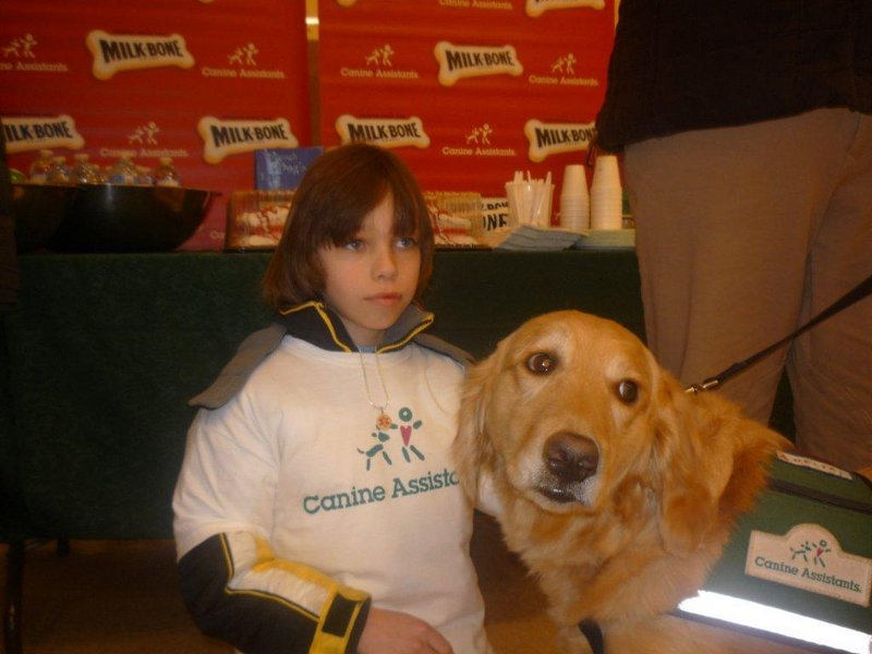 Seth Richards, who has epilepsy, spends time with a service dog similar to one he will be paired with once he is trained.