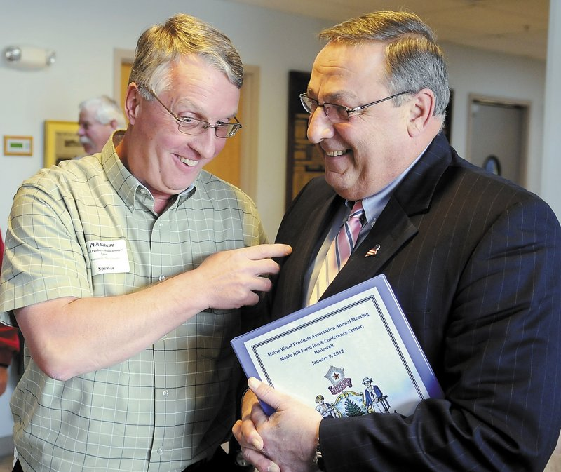 Phil Bibeau, left, of Westminster, Mass., talks with Gov. Paul LePage on Monday at the Maine Wood Products Association meeting in Hallowell.