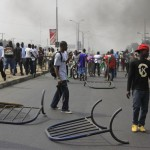 People walk past barricades mounted in Lagos, Nigeria, on Monday. A national strike paralyzed much of the nation.