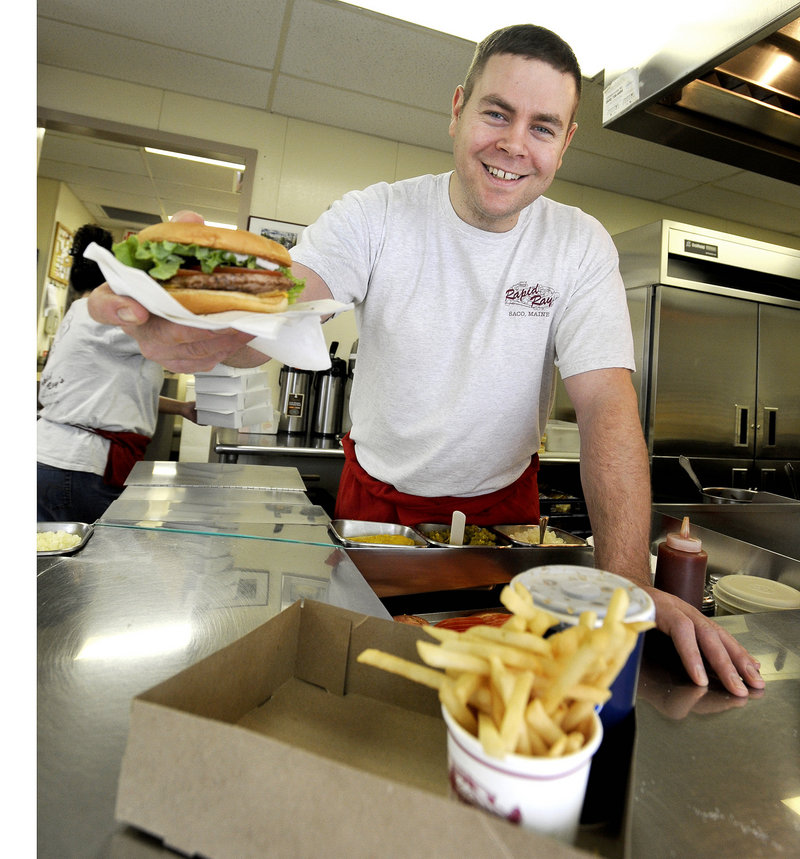 "Robert Roberge, grandson of founder Renald ""Ray"" Camire, serves up a Rapid Ray's cheeseburger."