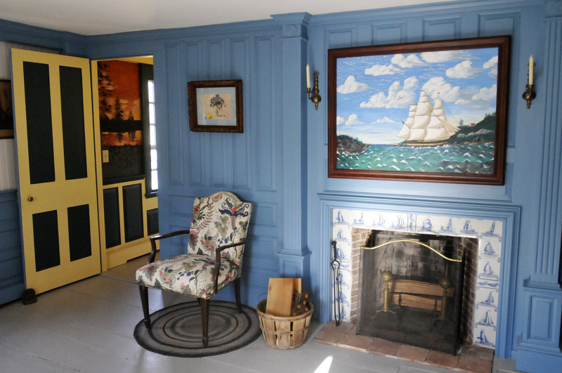 An upstairs bedroom boasts a fireplace bordered with Dutch tiles and a painting by Marjorie Cantara.