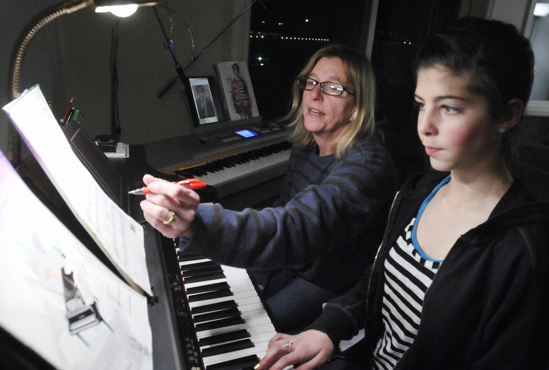 Denise Calkins gives a piano lesson last week to Amelia Papi, 12, of South Portland on a keyboard donated to her so she could continue teaching. Calkins received dozens of offers of replacement instruments after losing two pianos in a fire in November.