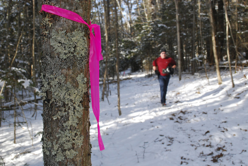 Volunteers from the Acadia Trail Runners mark trees every 10 meters along the course to prevent racers from getting lost.