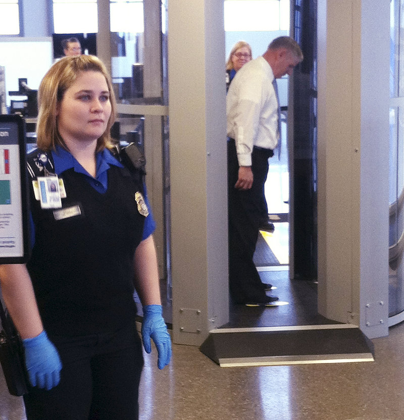 TSA screener Kayla Kelly stands near the new scanners, while behind her TSA screener Gordon Field is scanned.