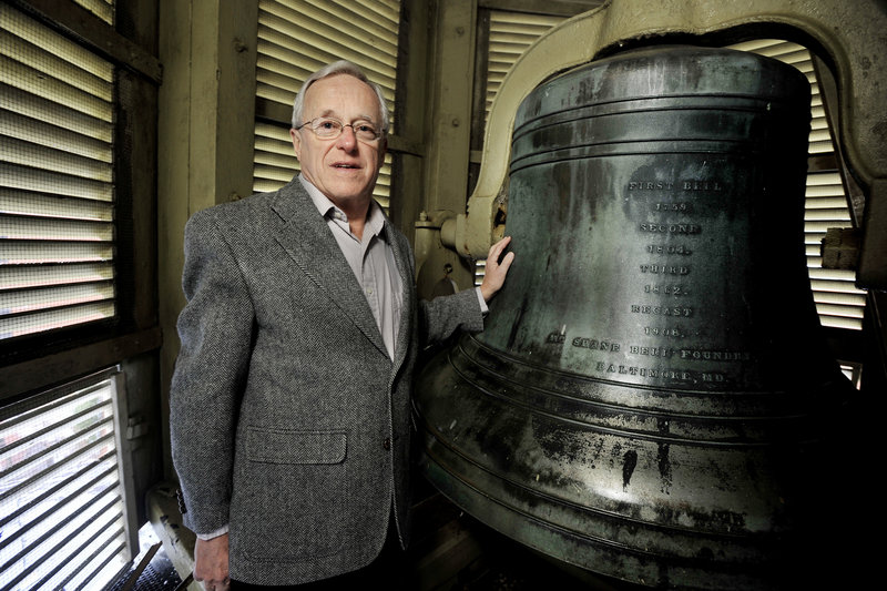 Stephen Jenks, president of the board of trustees of Portland's First Parish Church, stands in the steeple with the church's bell, which is its third.