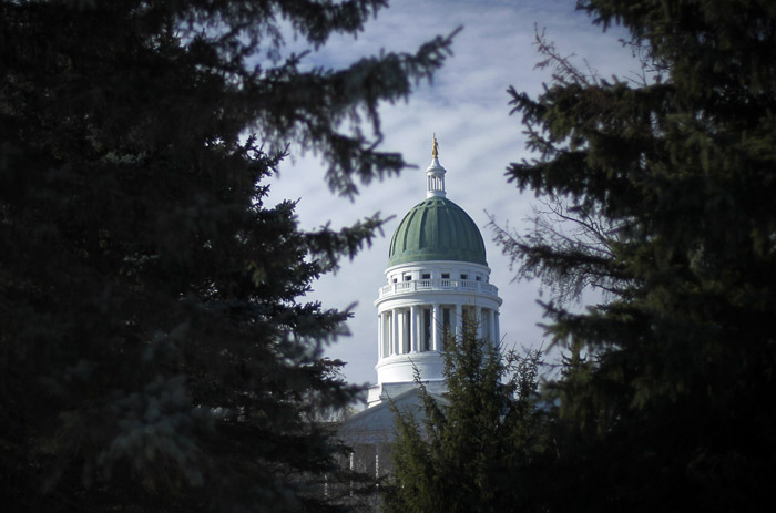 The Maine State House is framed by spruce trees in Capitol Park in Augusta. The House and Senate opening bells ring at 10 a.m. on Wednesday.