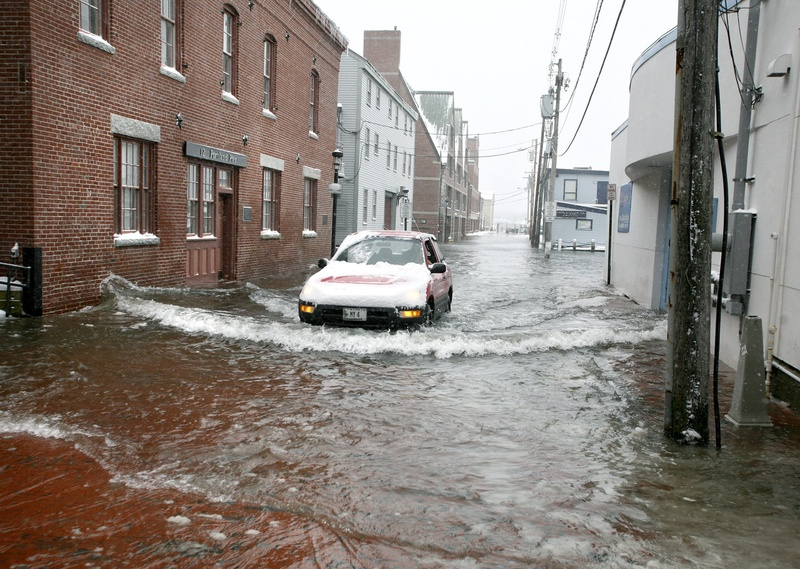 A car drives slowly through the water at high tide on Portland Pier on Jan. 2, 2010. Portland's wharfs and piers are among the areas of the city that could be under water by the end of this century due to higher sea levels brought about by climate change, according to a risk analysis for the city.