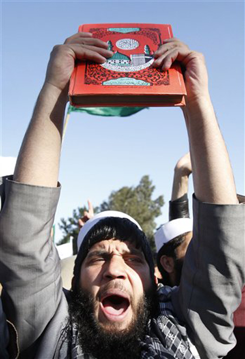 An Afghan protester holds a copy of Islam's holy book Quran as he shouts slogans during an anti-US demonstration in Jalalabad, east of Kabul, Afghanistan, on Wednesday.