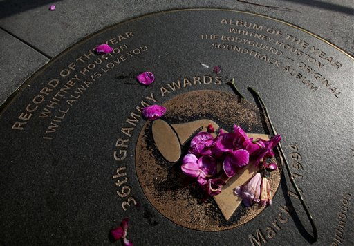 Flowers are placed on a sidewalk plaque honoring Whitney Houston's Grammy wins in 36th Grammy Awards, outside the Grammy Museum in Los Angeles.