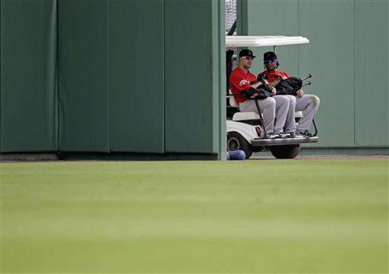 Boston Red Sox's Ryan Kalish, left, and Darnell McDonald are driven out of the ball park on a golf cart to a practice field during a baseball spring training workout Tuesday, Feb. 28, 2012, in Fort Myers, Fla. (AP Photo/David Goldman)