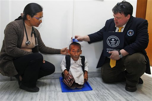 Editor in Chief of Guinness World Records Craig Glanday, right, and Dr. Kashila Pradhan, left, officially measure Nepal's Chandra Bahadur Dangi, 72, who says he's only 22 inches (56 centimeters) tall, at the CIWEC clinic in Katmandu, Nepal, Sunday, Feb. 26, 2012. (AP Photo/Niranjan Shrestha)