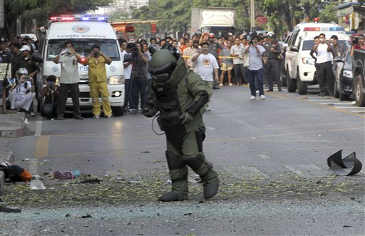 A Thai explosive disposal official examines the site today of one of the two explosions that boomed through a busy Bangkok neighborhood.