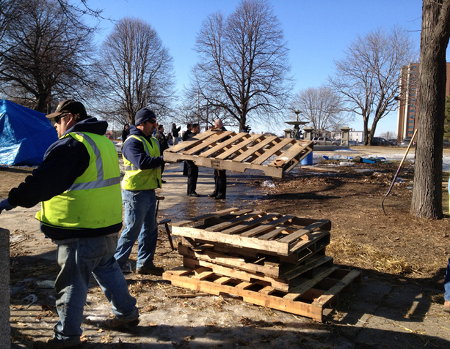 Portland Public Services employees stack pallets for removal by a forklift today in Lincoln Park. Occupy Maine protesters had used the pallets as platforms for their tents.