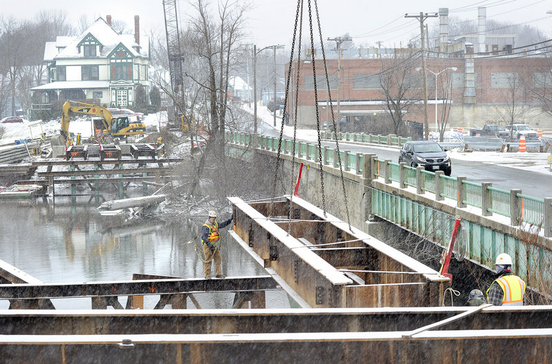 Reed & Reed construction workers build a temporary bridge across the Presumpscot River in Westbrook on Tuesday, a project that will allow traffic to flow while the old, adjacent bridge on Cumberland Street is replaced. The old bridge is to be replaced and ready for use by 2014.