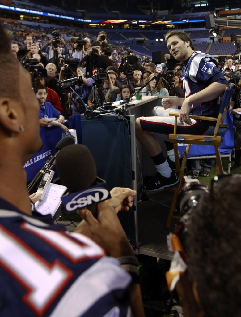 New England Patriots quarterback Tom Brady answers a question from teammate Tiquan Underwood during Media Day for NFL football's Super Bowl XLVI on Tuesday in Indianapolis.