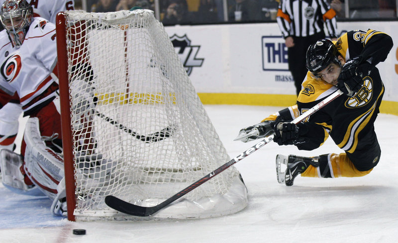 Patrice Bergeron of the Bruins tries to center the puck from behind the net as Carolina goaltender Cam Ward protects the net Thursday night. The Hurricanes beat Boston for the fourth time in four tries this season, 5-0.