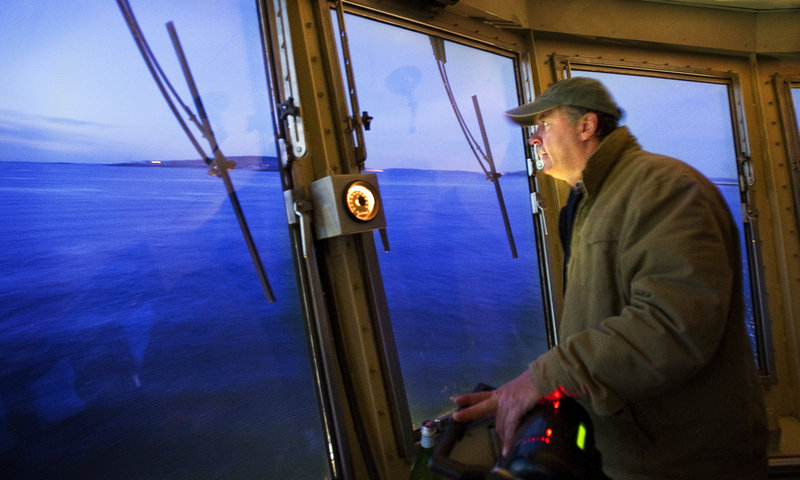 Gene Willard peers out into a pre-dawn sea of blue on his morning ferry run to the islands.