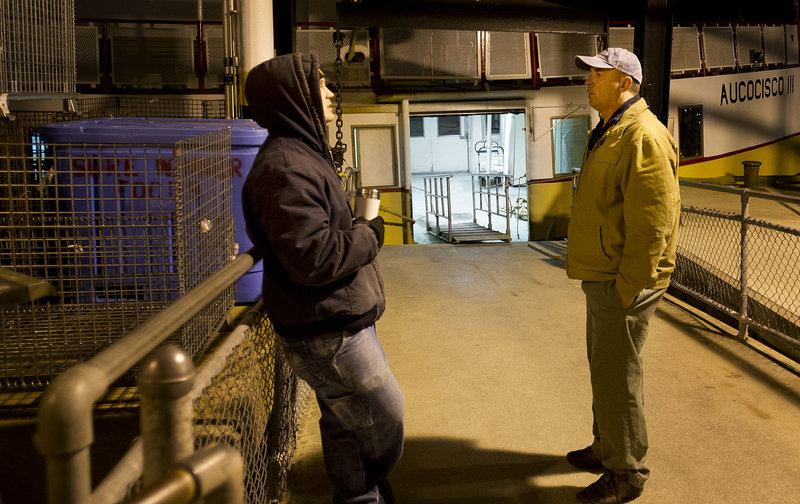 Gene Willard talks with deckhand Andy Gildart, left, at 4:56 a.m., before boarding the Aucocisco II for the morning run to the islands.